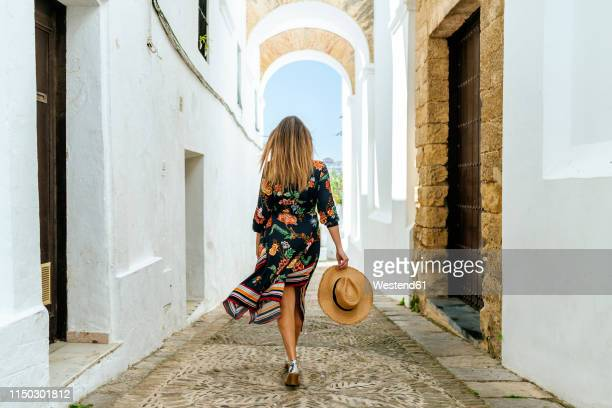spain, cadiz, vejer de la frontera, back view of fashionable woman walking through passage - andalucia fotografías e imágenes de stock