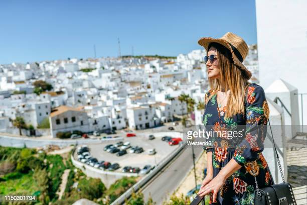spain, cadiz, vejer de la frontera, fashionable woman standing on roof terrace looking at view - floral pattern dress stock pictures, royalty-free photos & images