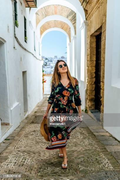 spain, cadiz, vejer de la frontera, fashionable woman walking through passage - open toe stock pictures, royalty-free photos & images