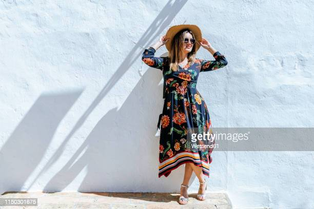 spain, cadiz, vejer de la frontera, fashionable woman with straw hat standing in front of white wall - sandal stock pictures, royalty-free photos & images