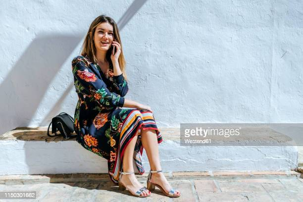 spain, cadiz, vejer de la frontera, portrait of fashionable woman on the phone sitting on wall - sandal stock pictures, royalty-free photos & images