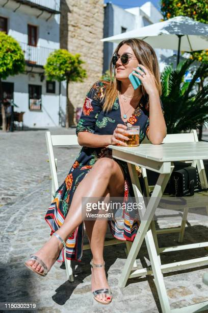 spain, cadiz, vejer de la frontera, young woman on the phone sitting at street cafe with glass of beer - sandal stock pictures, royalty-free photos & images