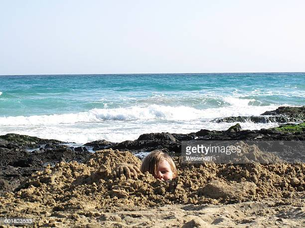 Spain, Canary Islands, Fuerteventura, boy at the sea buried in sand