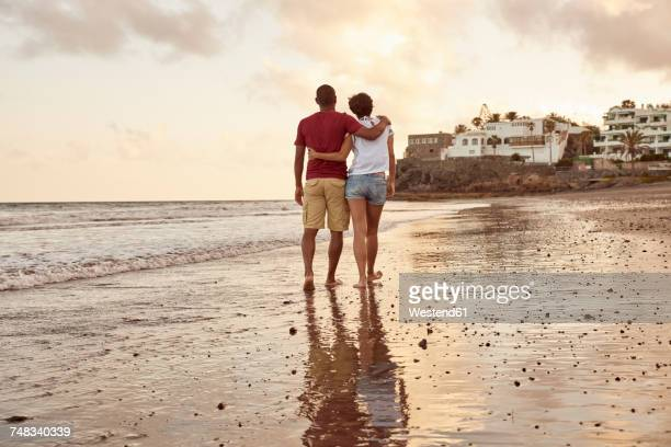 spain, canary islands, gran canaria, back view of couple in love walking on the beach - grand canary stock pictures, royalty-free photos & images