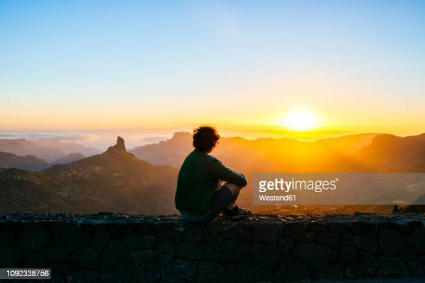 spain, canary islands, gran canaria, back view of man sitting on a wall watching sunset over mountainscape - cena de tranquilidade - fotografias e filmes do acervo