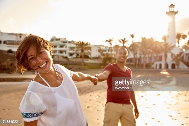Spain, Canary Islands, Gran Canaria, portrait of happy woman holding hand on the beach