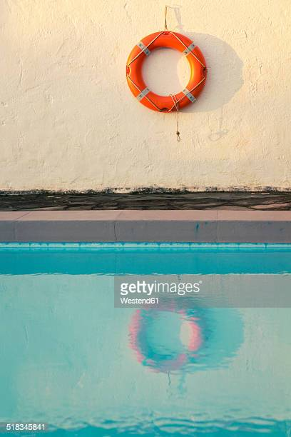 Spain, Canary Islands, La Palma, life saver hanging on wall behind swimming pool