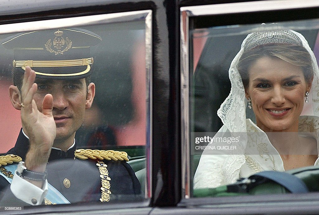 Spanish Crown Prince Felipe of Bourbon waves to the crowd next to his wife Princess of Asturias Letizia Ortiz aboard the Rolls Royce during their parade through the streets of Madrid 22 May 2004.