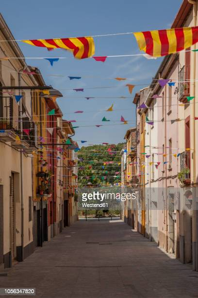 spain, catalonia, alley with catalonian flags - catalonië stockfoto's en -beelden