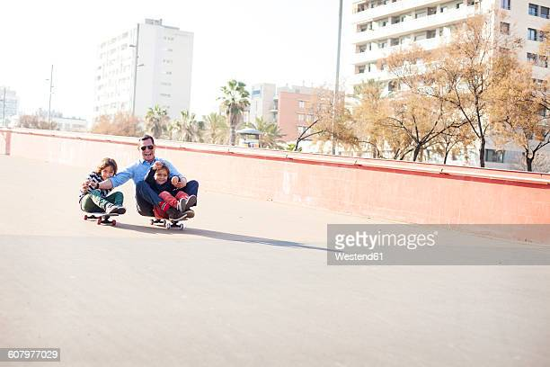 Spain, Catalonia, Barcelona, Uncle and kids doing skate board