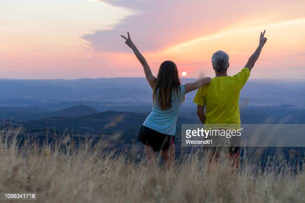 spain, catalonia, montcau, happy senior father and adult daughter looking at view from top of hill during sunset - pareja hombre mayor y mujer joven fotografías e imágenes de stock