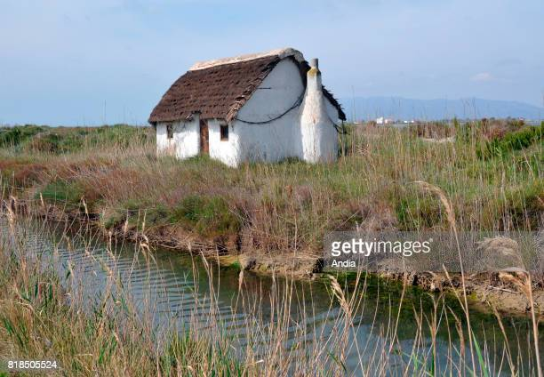 the Ebro Delta Nature Park part of the Unesco Biosphere Reserve network Fishing hut with whitewashed walls by a canal totally built with local...