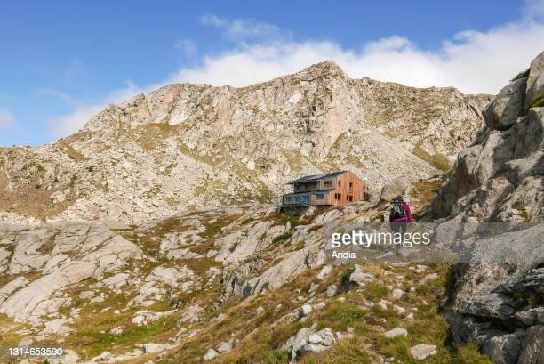 Vall Fosca. Aoguestortes y Sant Maurici National Park. Hiker, woman with an backpack and a pair of walking poles arriving at Colomina refuge by Lake...
