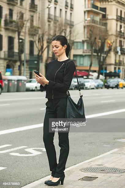 Spain, Catalunya, Barcelona, young black dressed businesswoman telephoning in front of a street