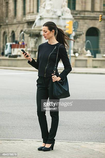 Spain, Catalunya, Barcelona, young black dressed businesswoman looking at her smartphone in front of a street