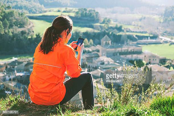 spain, catalunya, orista, young female jogger having a break using smartphone - center athlete stock pictures, royalty-free photos & images
