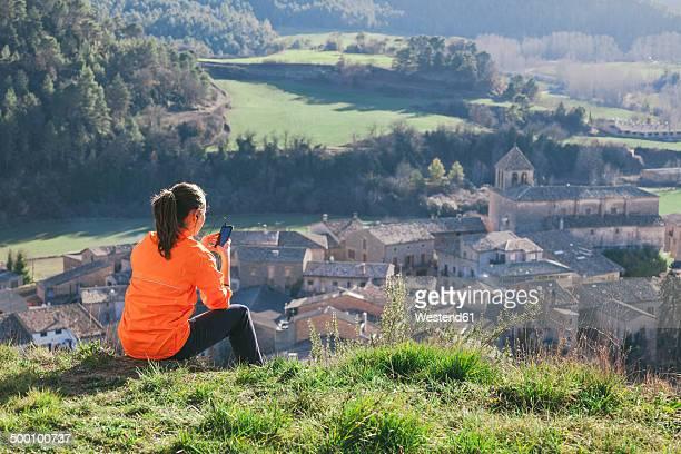 Spain, Catalunya, Orista, young female jogger having a break using smartphone