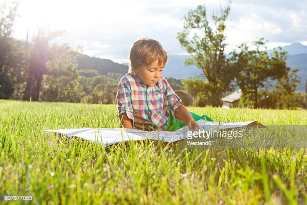 Spain, Cerdanya, little boy on a meadow looking at map