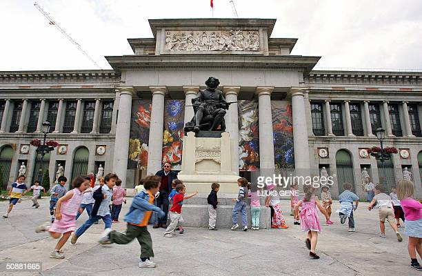 Children play around the statue of Velasquez in front of the Prado museum 21 May 2004 in Madrid Spanish Crown Prince Felipe of Bourbon will marry...