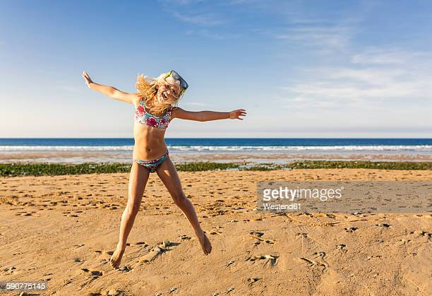 Spain, Colunga, little girl with diving mask jumping in the air on the beach