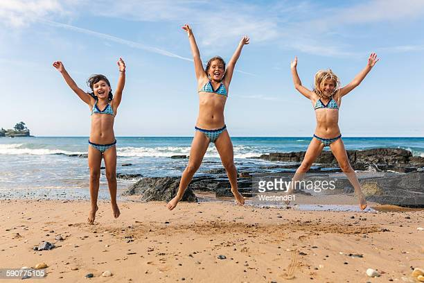 Spain, Colunga, three girls jumping in the air on the beach