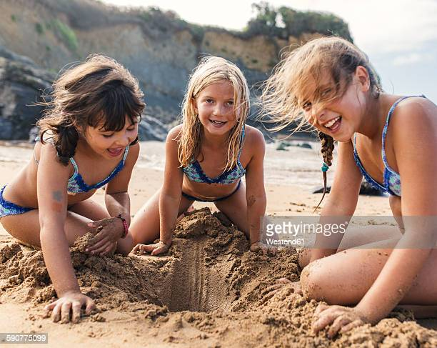 Spain, Colunga, three girls playing on the beach