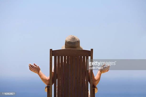 Spain, Costa Blanca, Rear view of woman sitting on wooden chair, facing sea