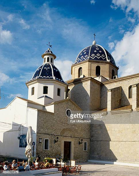 Spain Costa Blanca Valencia Alicante Province Altea Church with blue tiled roof in the square with tourists sat outside cafe in foreground