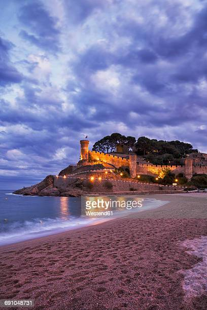 Spain, Costa Brava, Tossa de Mar, main beach and old town wall at dusk
