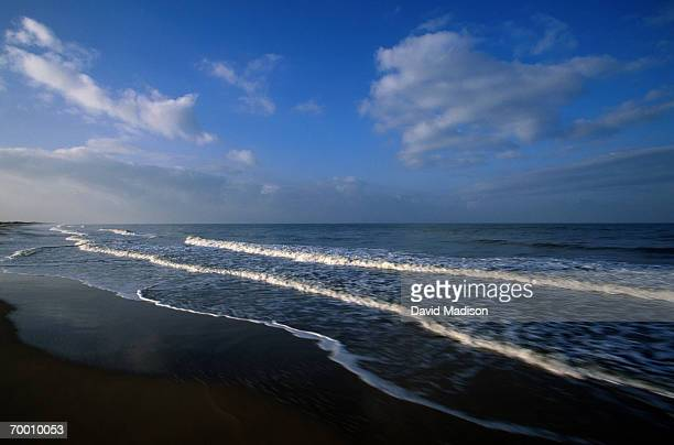 Spain, Donana National Park, waves rolling onto beach