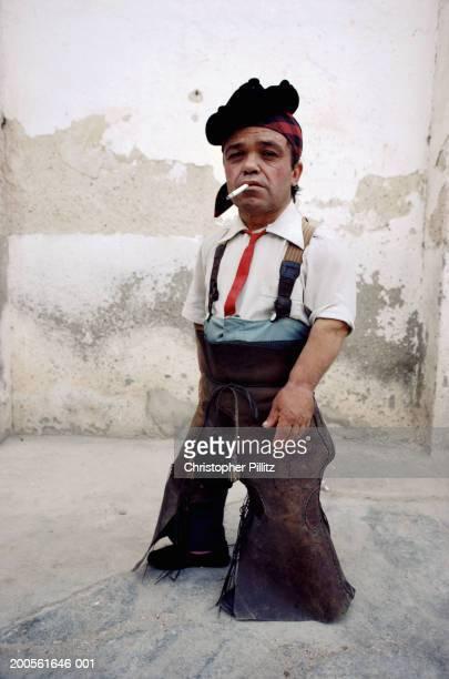 Spain, dwarf bullfighter smoking cigarette