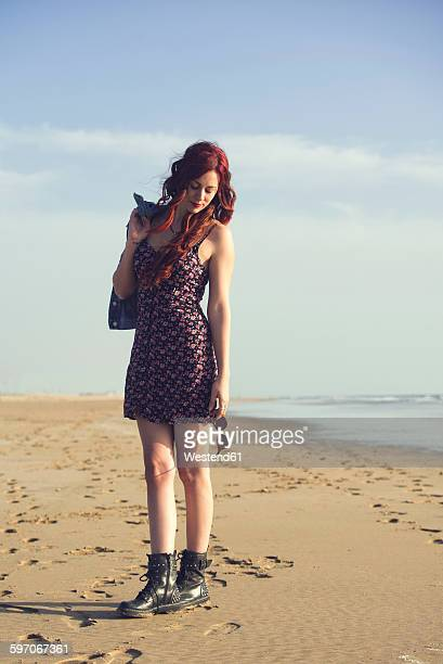 Spain, El Puerto de Santa Maria, portrait of redheaded young woman standing on the beach