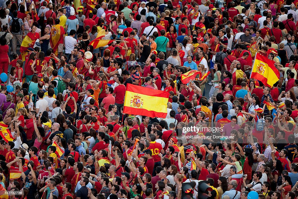 Spain fans fly the national flag as crowds of wait to celebrate with the players as they parade the UEFA EURO 2012 trophy on a double-decker bus on July 2, 2012 in Madrid, Spain. Spain beat Italy 4-0 in the UEFA EURO 2012 final match in Kiev, Ukraine, on July 1, 2012.