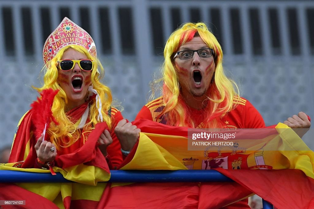 TOPSHOT - Spain fans sporting wigs and a kokoshnik (traditional Russian headdress) cheer before the Russia 2018 World Cup Group B football match between Spain and Morocco at the Kaliningrad Stadium in Kaliningrad on June 25, 2018. (Photo by Patrick HERTZOG / AFP) / RESTRICTED