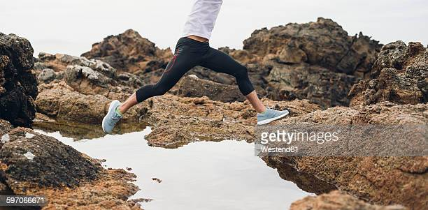 Spain, Ferrol, jogger jumping over water at the coast.
