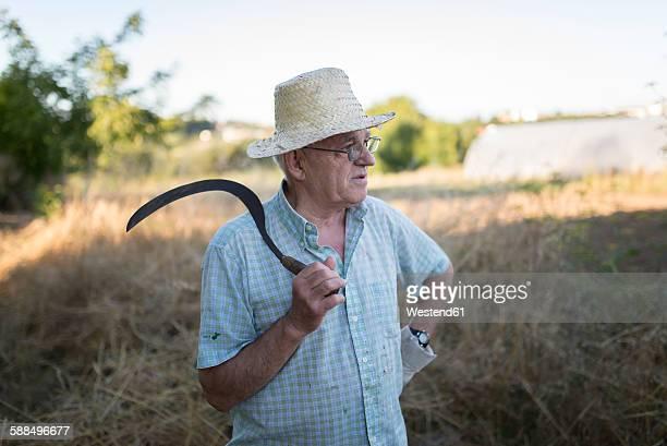 Spain, Ferrol, portrait of a farmer with scythe on his shoulder