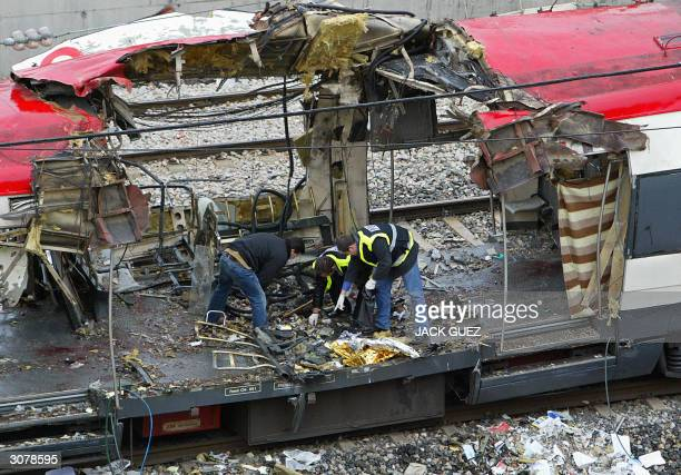 Forensic experts inspect the train which exploded the day before 12 March 2004 at the Atocha train station At least 198 people were killed and more...