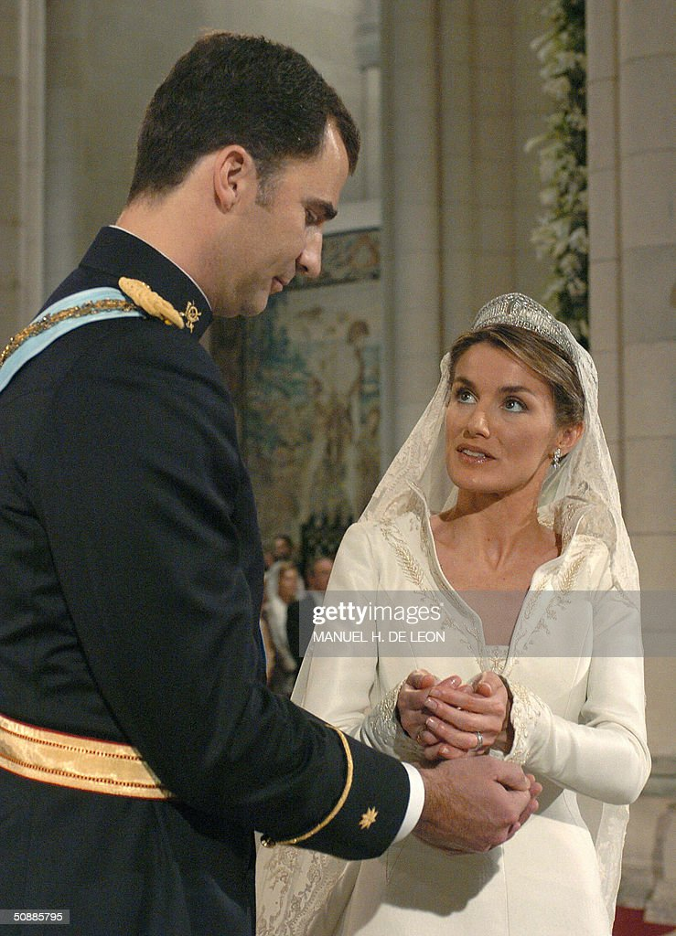Former journalist Letizia Ortiz puts the ring onto the finger of Spanish Crown Prince Felipe of Bourbon during their wedding ceremony at Madrid's Almudena Cathedral 22 May 2004.