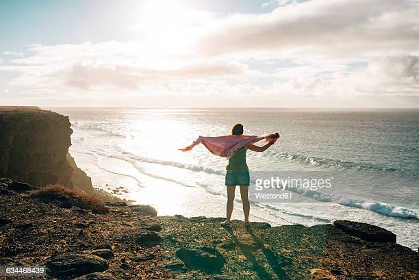 Spain, Fuerteventura, El Cotillo, back view of woman looking to the sea