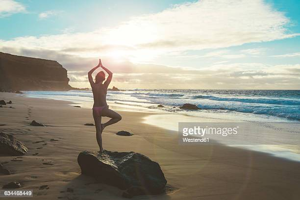 Spain, Fuerteventura, El Cotillo, back view of woman practicing yoga on the beach at sunset