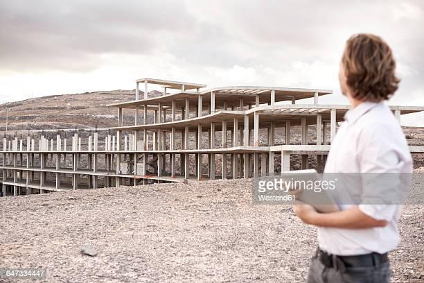 Spain, Fuerteventura, Jandia, architect looking at building shell