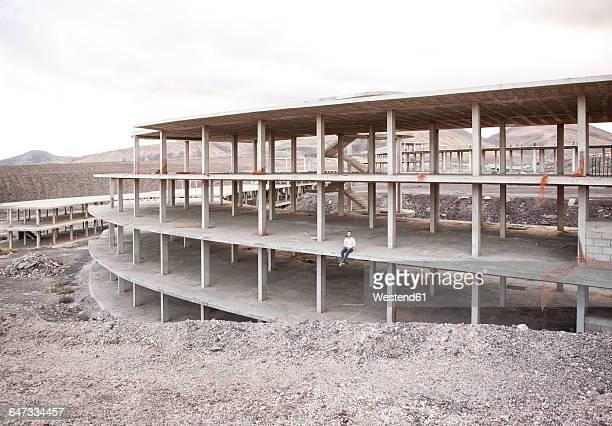 Spain, Fuerteventura, Jandia, architect sitting in building shell