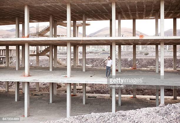 Spain, Fuerteventura, Jandia, architect standing in building shell