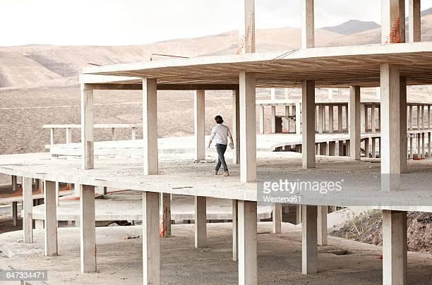 Spain, Fuerteventura, Jandia, architect walking in building shell