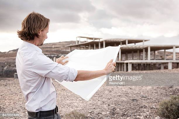 Spain, Fuerteventura, Jandia, architect with blueprint at building shell