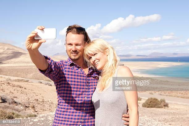 Spain, Fuerteventura, Jandia, couple taking selfie at the coast
