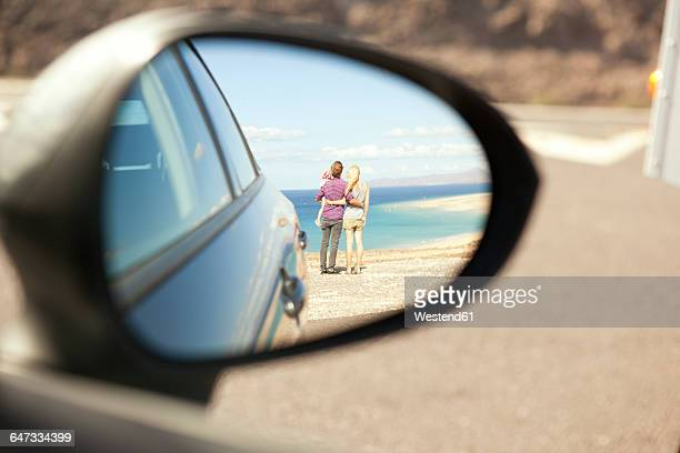 spain, fuerteventura, jandia, reflection of family at the coast in wing mirror of a car - side view mirror stock photos and pictures