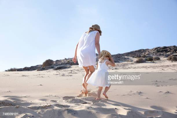 Spain, Fuerteventura, mother walking with daughter on the beach