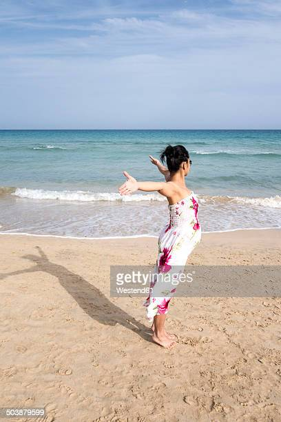 Spain, Fuerteventura, Pregnant woman with outstretched arms on beach