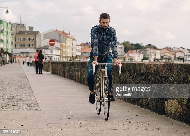Spain, Galicia, Ares, hipster man riding with a fixie bike